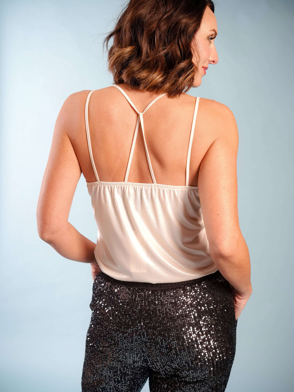 Iridescent soft beige v-neck modern camisole, Back crisscross straps,  Model is wearing a small/medium.