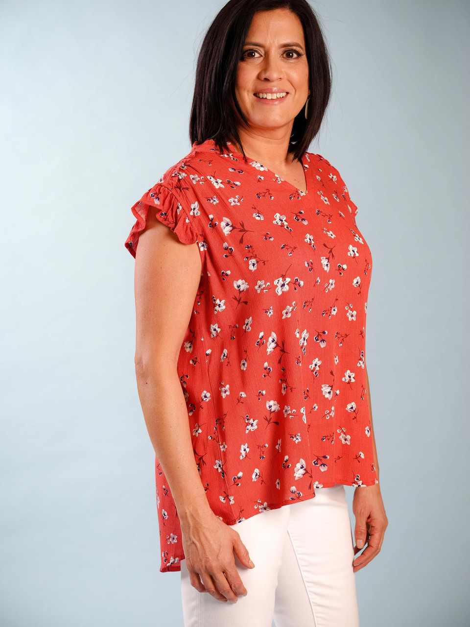 Rusty-red top with floral pattern, V-neck with delicate ruffled collar and sleeves, Slight high/low hem, Model is wearing a small.