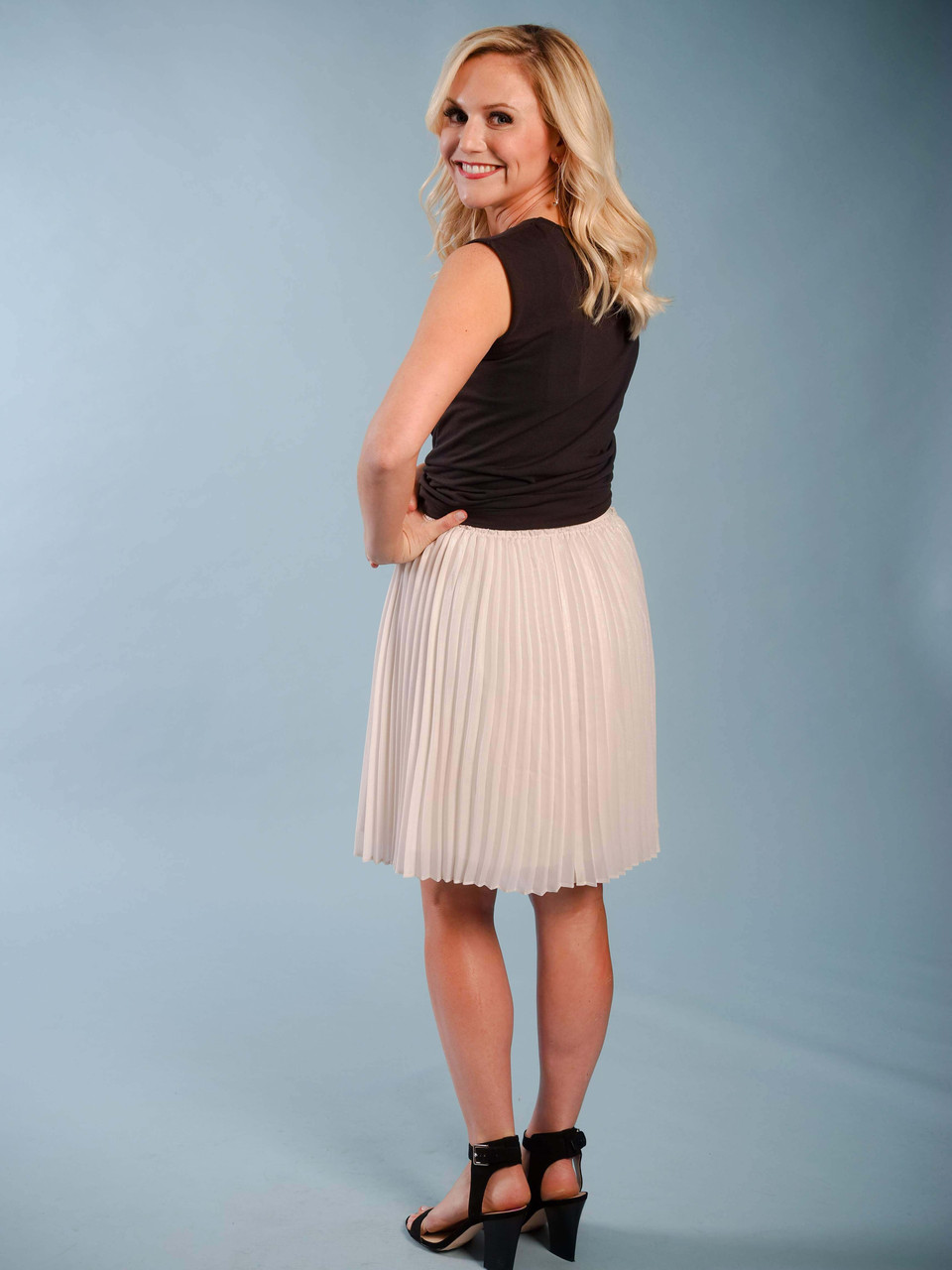 Feminine mini lined pleated skirt in nude with a subtle shimmer, Elastic waist, Could be dressed up or down,  Model is wearing a XS/S.