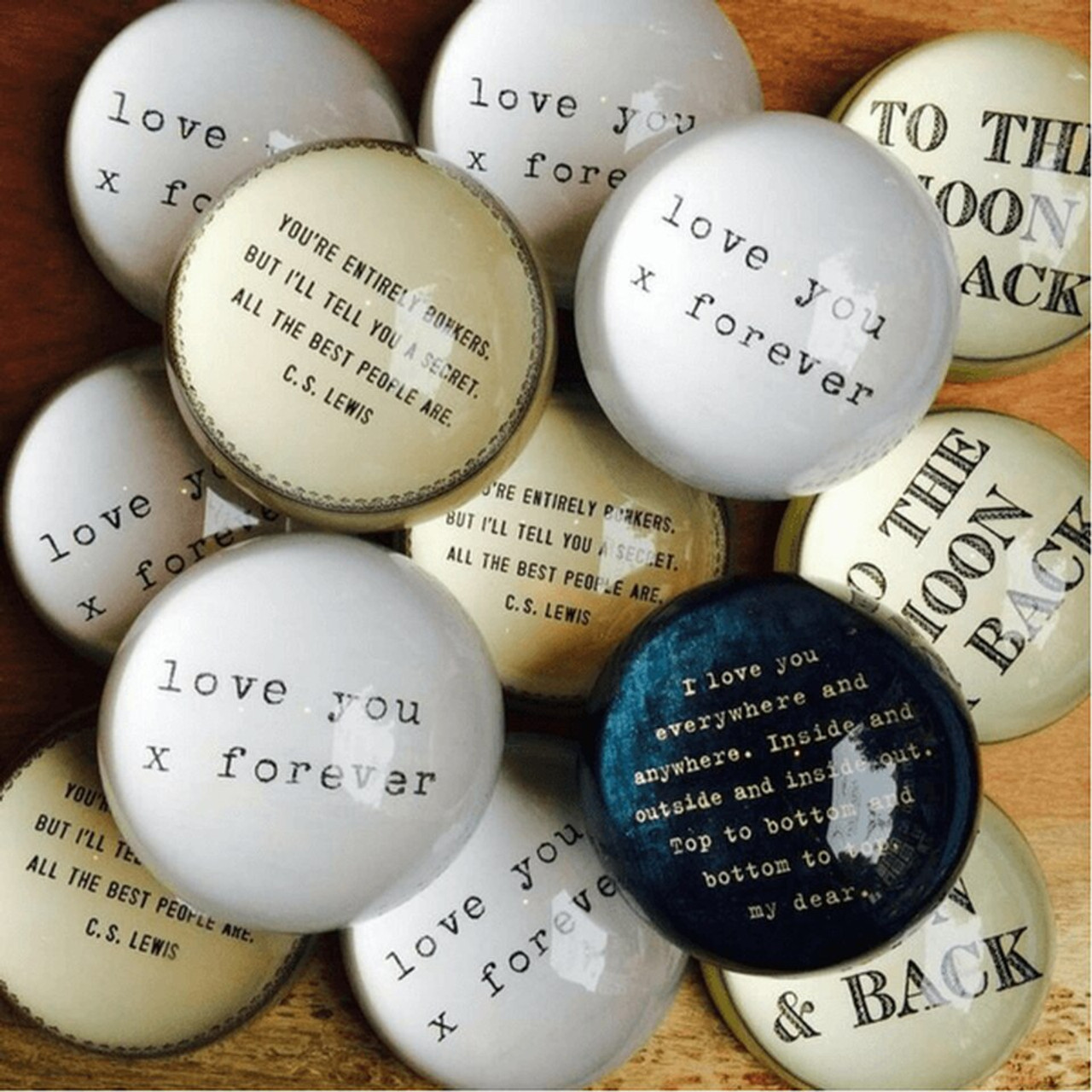 """This classic paperweight features a decorative border and a quote from Lewis Carroll: """"You're entirely bonkers. But I'll tell you a secret. All the best people are."""""""