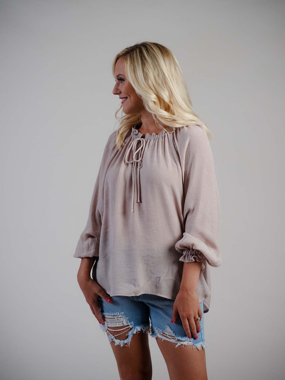 blush top with ruffle neck and tied neck