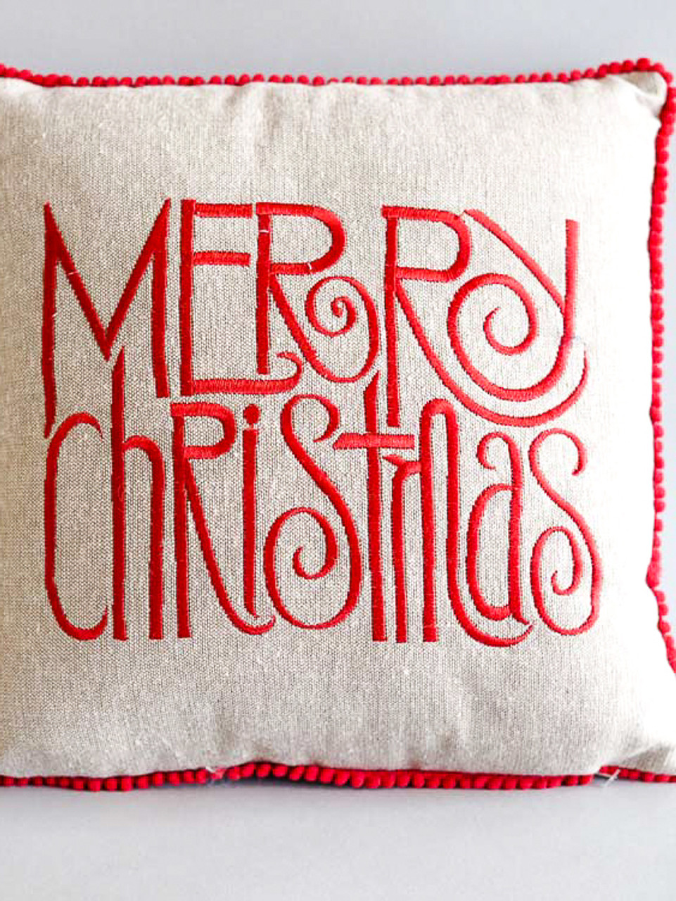 Merry Christmas pillow with red pom-pom fringe