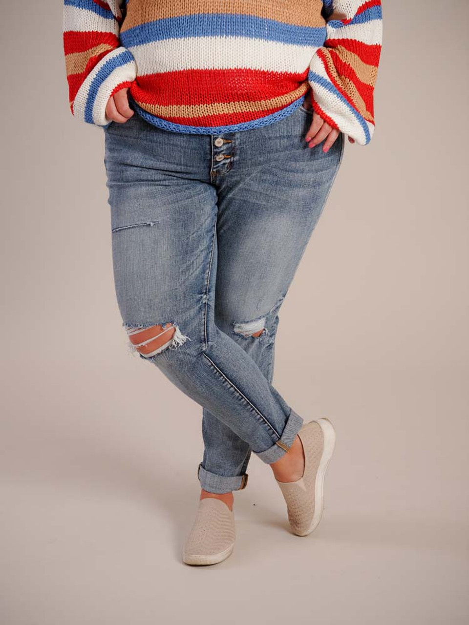 Medium blue denim jeans with a laid back worn-in look. Front and back pockets, 5 button fly, torn detail on right thigh and frayed knees