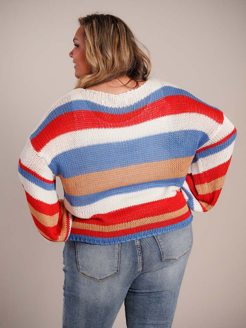 Loose knit sweater with with fun varying cream, blue, red, and gold stripes