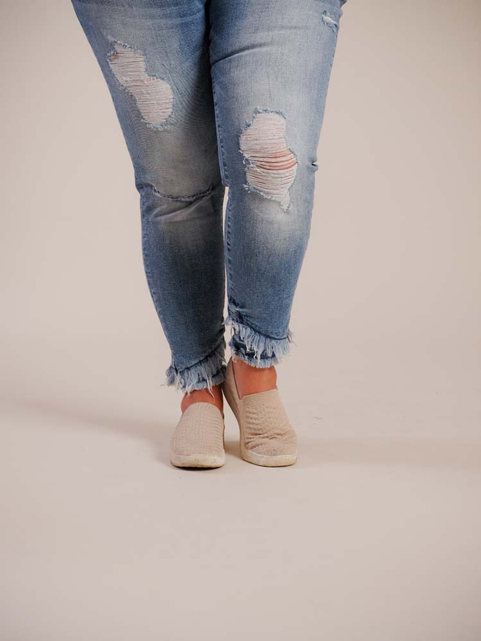 Medium/light blue denim skinny jeans with frayed details. Front and back pockets, zipper fly, and layered frayed detail at ancles