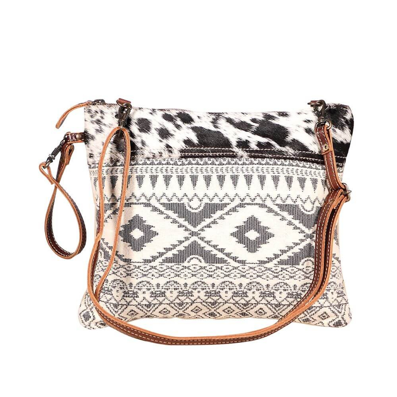 This crossbody bag wears a vintage look to add charm to your vivacious personality. The cow hide detail and ethnic rug pattern make for a beautiful look. Two strap options make it a must – have. The back is light tan denim. Zipper close at top; interior is fully lined and has one zipper pocket and two slip pockets.