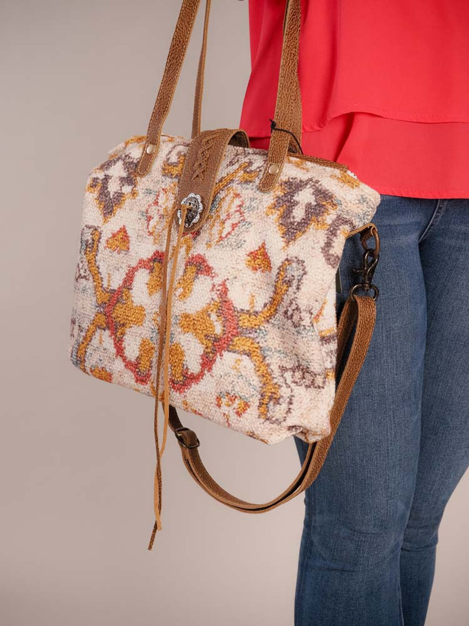 unique patterns in a way that is easy on the eye. It comes with a detachable crossbody strap and will make a standout addition to your collection. Zipper close at top, decorative leather magnet snap closure with silver tone metal button and leather string tie, zipper pocket on back; interior is fully lined and has one zipper pocket and two slip pockets.