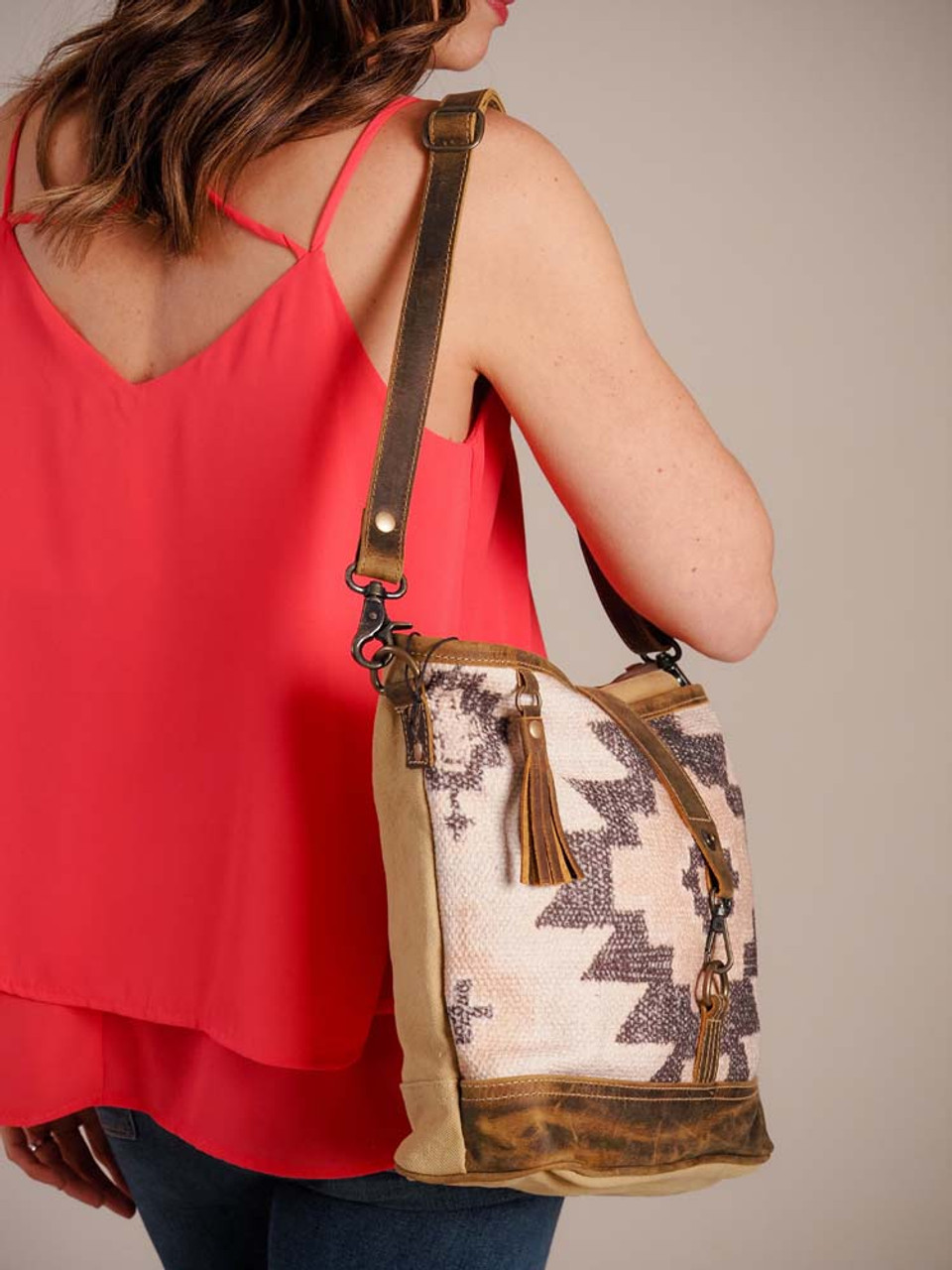 Fancy clasp and leather tassel on an alluring rug pattern, edged with at leather bottom and mustard denim on back and base. Detachable crossbody strap, zipper close at top, zipper pocket on back. Interior is fully lined and has one zipper pocket and two slip pockets.