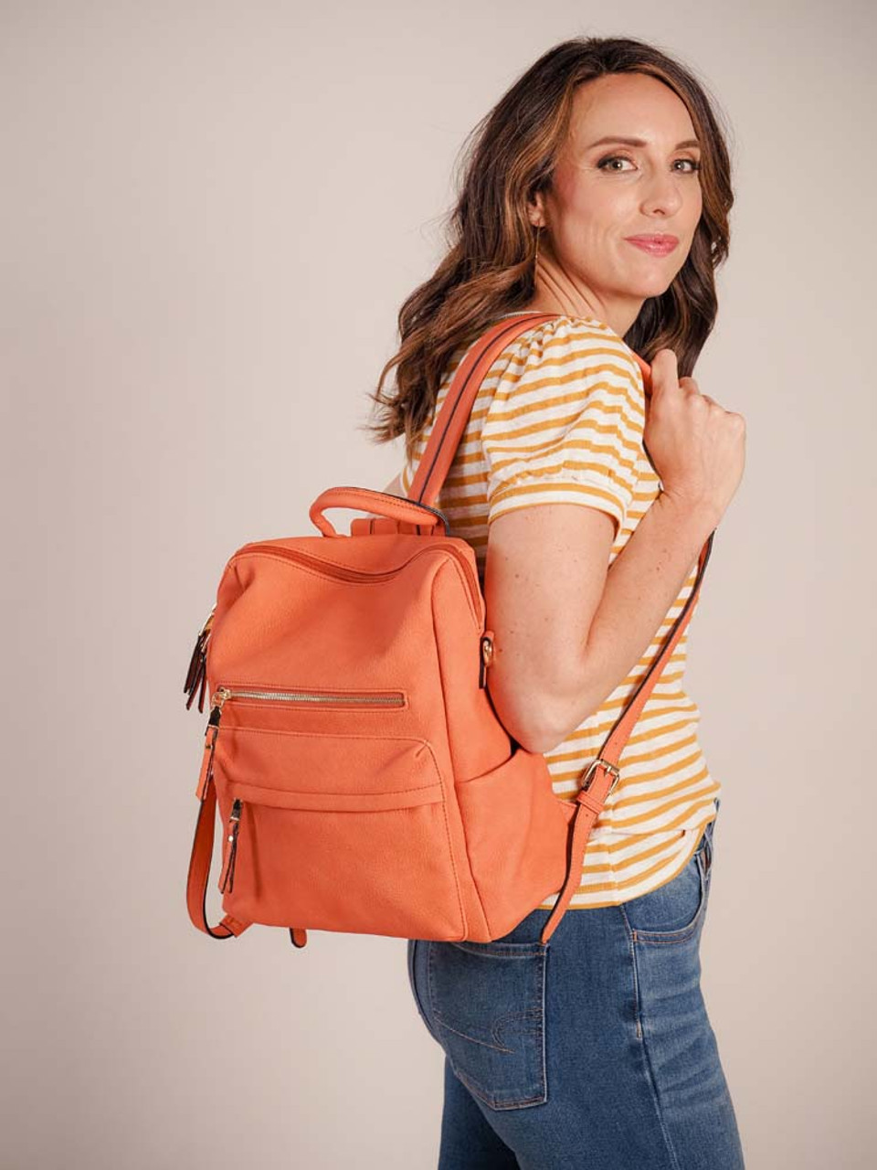 Convertible vegan leather backpack with handle at top, adjustable shoulder straps, and removable multi-color southwest geometric print guitar strap. Zipper close at top, 2 zipper pockets on front, slip pockets on sides, and zipper pocket on back. Interior is fully lined and has one zipper pocket and two slip pockets.