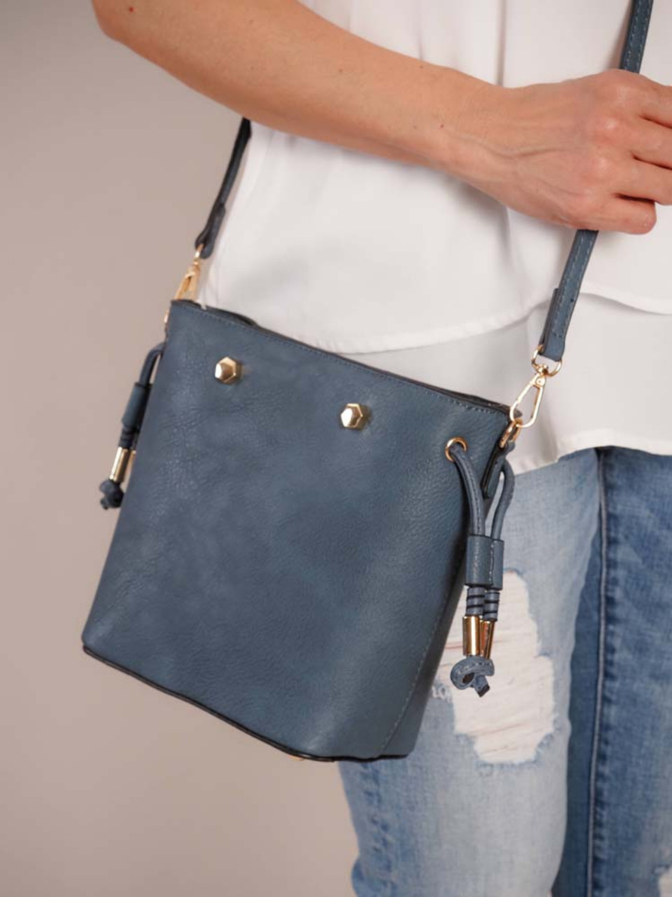 Indigo vegan leather with black edging and gold hardware. Includes an adjustable/detachable strap. Features card slots and a slip pocket inside and zip pocket on the outside. Use the snap closure and pull the side drawstrings to keep your items secure!