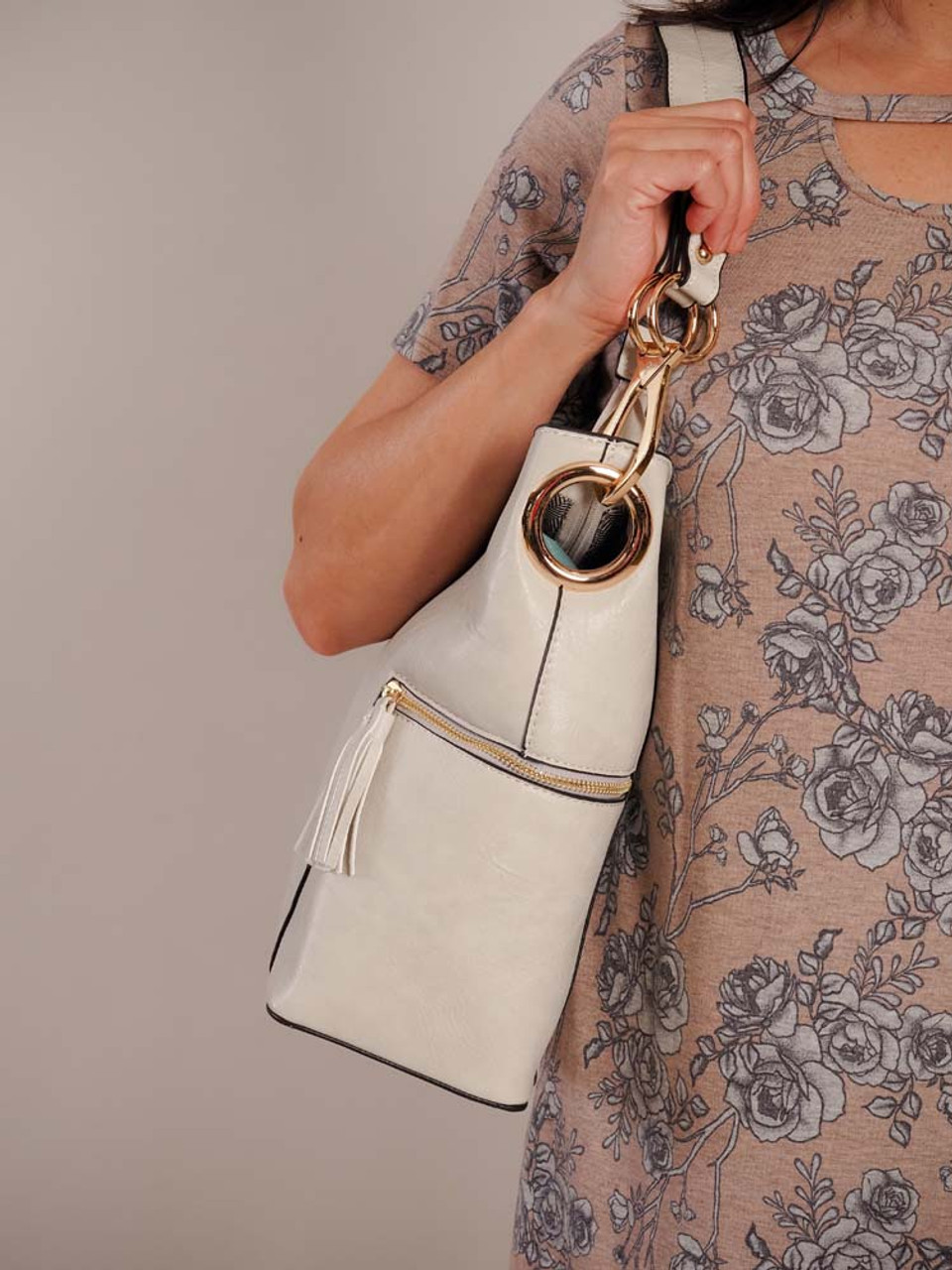 Soft greyish ivory vegan leather tote with black edging at seams and gold tone hardware. Zipper close at top and side pockets with tasseled zipper close. Choose to use the shoulder strap or the adjustable crossbody strap. Inside is fully lined and features two slip pockets, 2 zipper pockets, and a small compartment to keep your items accessible.