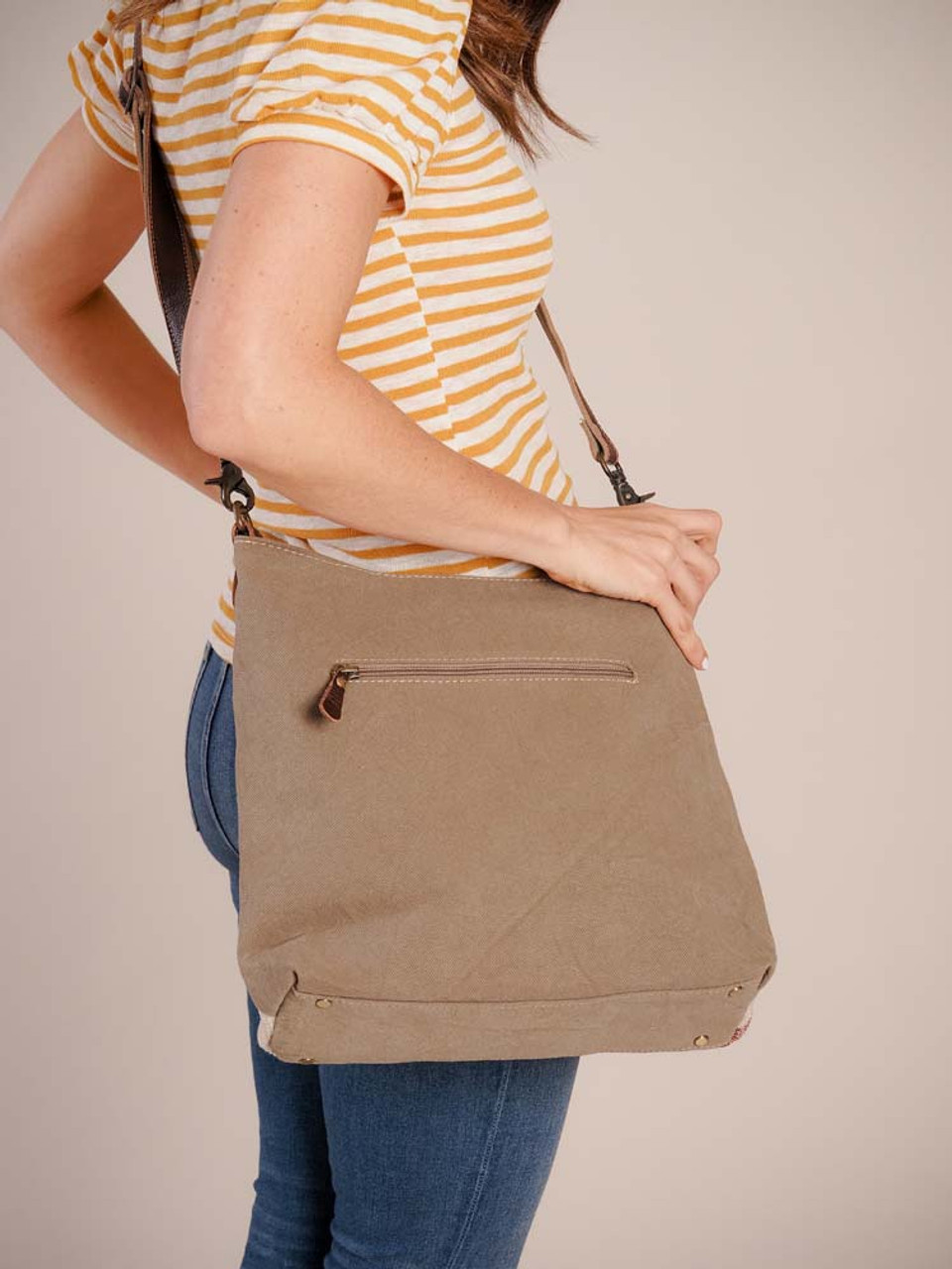 This shoulder bag is designed with a creative flair with vibrantly colored up-cycled rug on the front, sustainable military tent canvas on the rear and base, and leather accents.