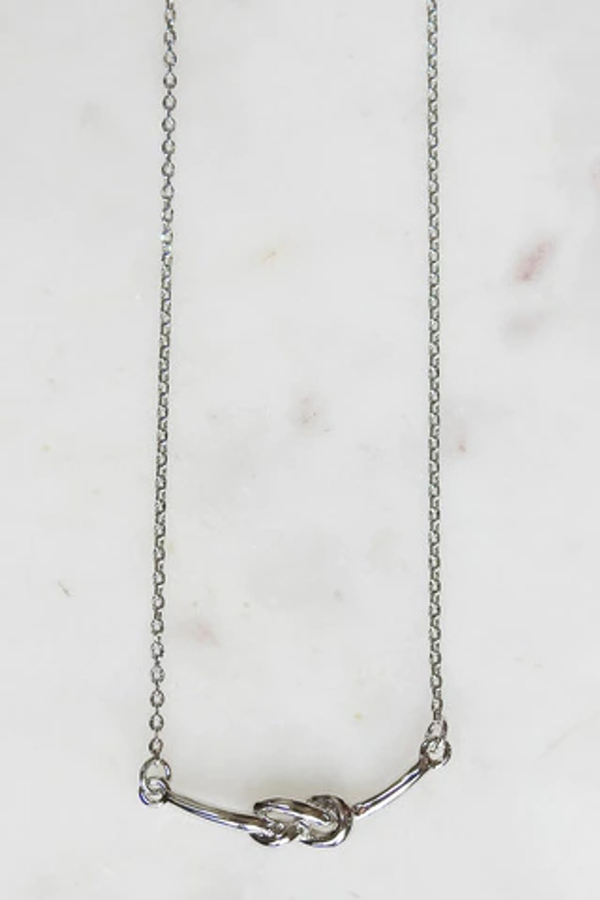 """This sweet white gold dipped knot necklace will have special meaning for whoever wears it. Nickel and lead free. Lobsterclaw clasp on dainty chain adjustable from 15.5"""" to 17.5""""."""