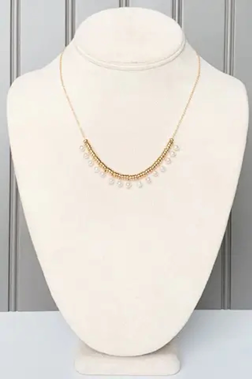 """Pearly white beads between goldtone spacers. Adjustable chain from 16""""-19"""" with lobsterclaw clasp. Nickel and lead free."""