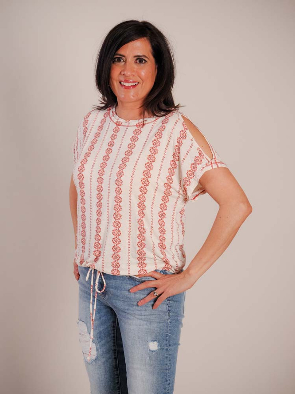 Loose fit lightweight heathered beige tshirt with red geometric and floral stripes. Unhemmed detail around neck and cold shoulders. Drawstring at bottom hem with matching cord