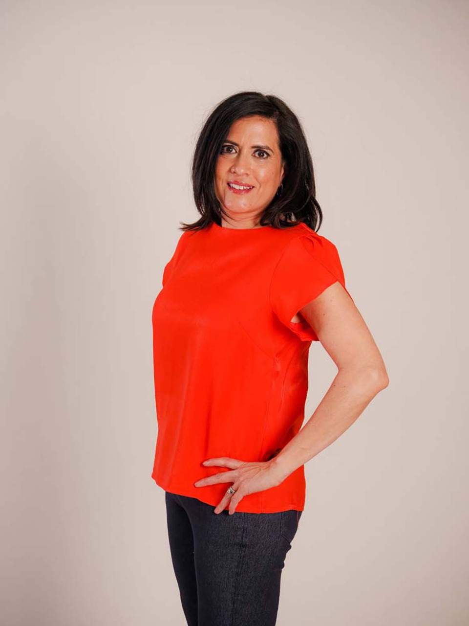 Beautifully bright orangey red blouse with a subtle sheen. Round neck; tulip sleeves; front darts for a taylored fit; golden button with loop closure in back