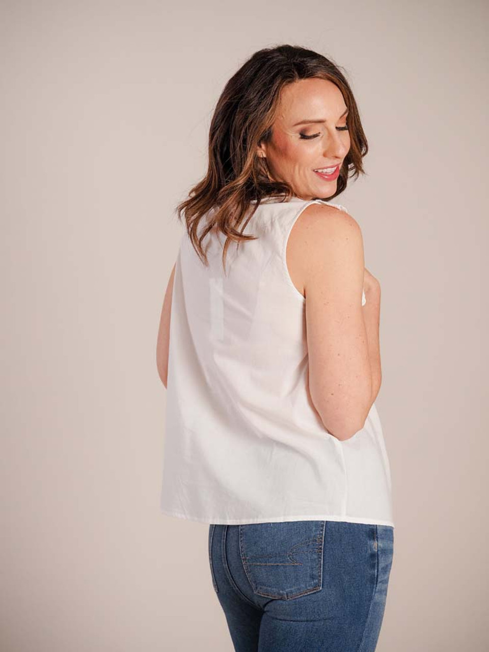 Pretty and lightweight blouse. Round neck with cord tie; eyelet lace front smock and ruffle detail; sleeveless
