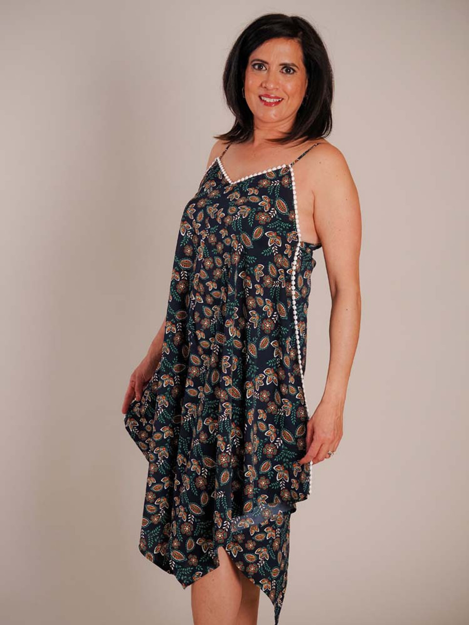 The material and design of this dress are flowy and flattering. Adjustable shoulder straps; v neck in front and back; white thread bead trim; asymetrical handkerchief shaped hem at bottom