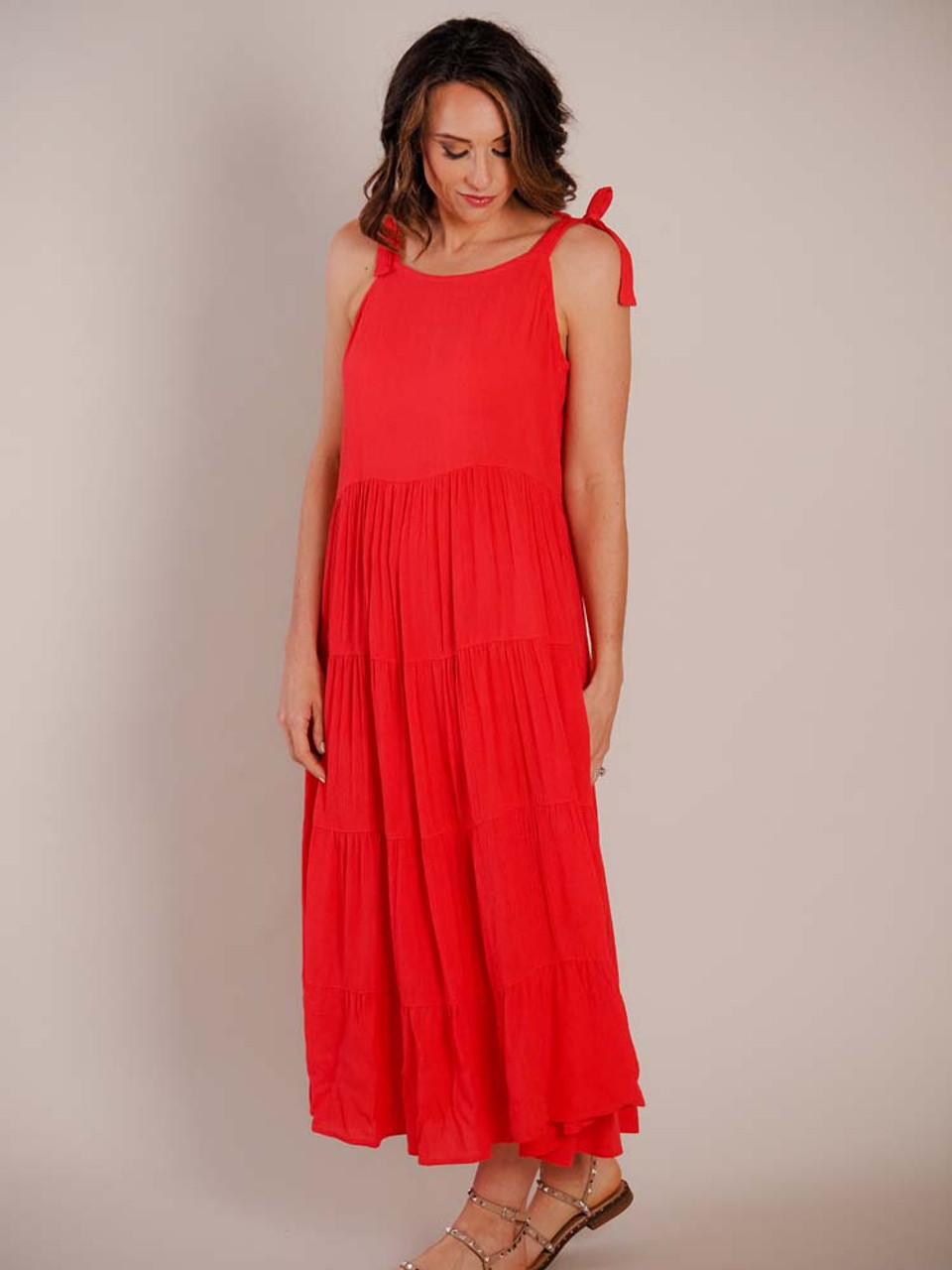 This beautiful coral red summer dress has tie straps; a straight neckline; softly pleated seam at waist; three more horizontal pleated seams down skirt