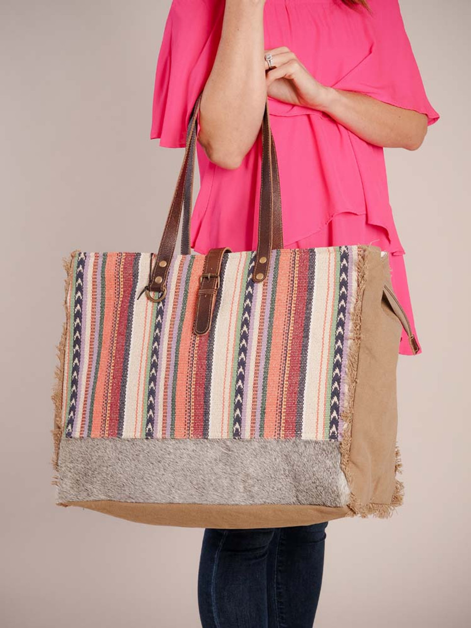 Intricately textured soft colores, this bag has enough room to accommodate all your essentials. It also has a strong canvas base so be assured of its sturdiness. Hairon at the front bottom; canvas back, sides, and bottom; freyed canvas trim; slip pocket on one side, zipper pocket on back; zipper close and strap with magnet button snap; double reinforced shoulder straps; fully lined inside with a zipper pocket and two slip pockets