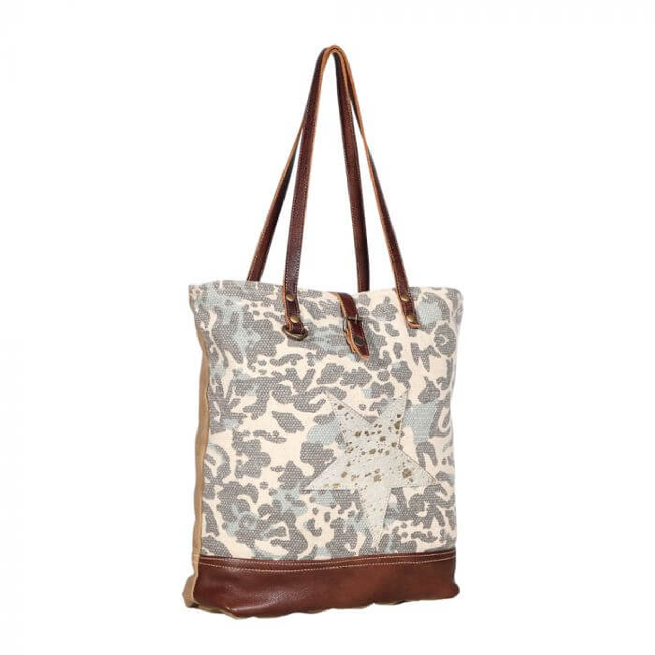 A spacious tote with an Americana look for your adventures. This bag gets its soul from canvas and rug and has its support system in double reinforced leather shoulder straps. Hairon star centerpiece with gold accents on the front; leather at bottom of front; canvas base, sides, and back; zipper pocket on back; zipper close and strap with magnet button snap; fully lined inside with a zipper pocket and two slip pockets