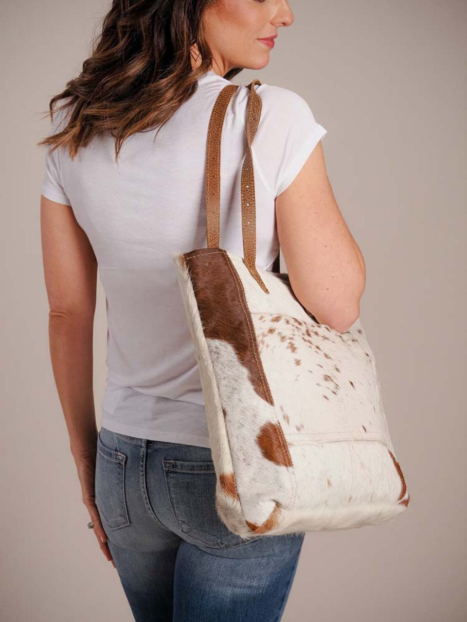 This white and brown hairon bag is the perfect to carry all your essentials. It is spacious, simple and chic. It is a pleasure to carry on your shoulder proportionately making it a style statement. Its has two flat genuine leather straps, a divided slip pocket in front and a zipper pocket in back; zippered top closure; fully lined inside with two slip pockets and a zipper pocket.