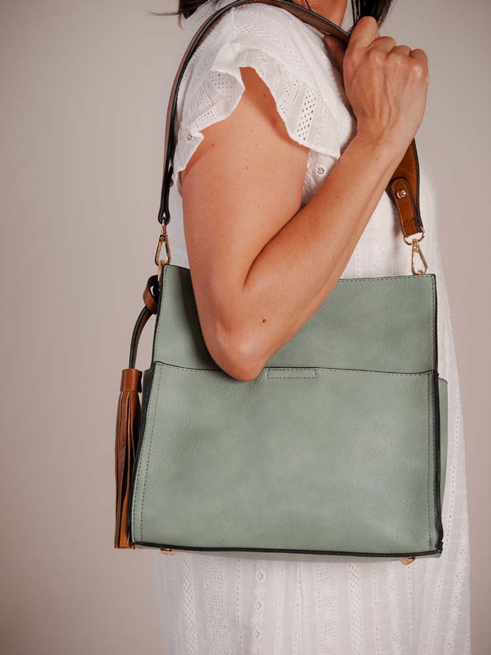 Lyla is a 2-in-1 style! Tote features a detachable guitar strap handle, decorative tassel, front slip pocket with magnet snap, slip pockets on the sides, and magnet snap close on top. Leave the matching colored small zipper-close bag inside for additional pockets including a zip pocket and two slip pockets!