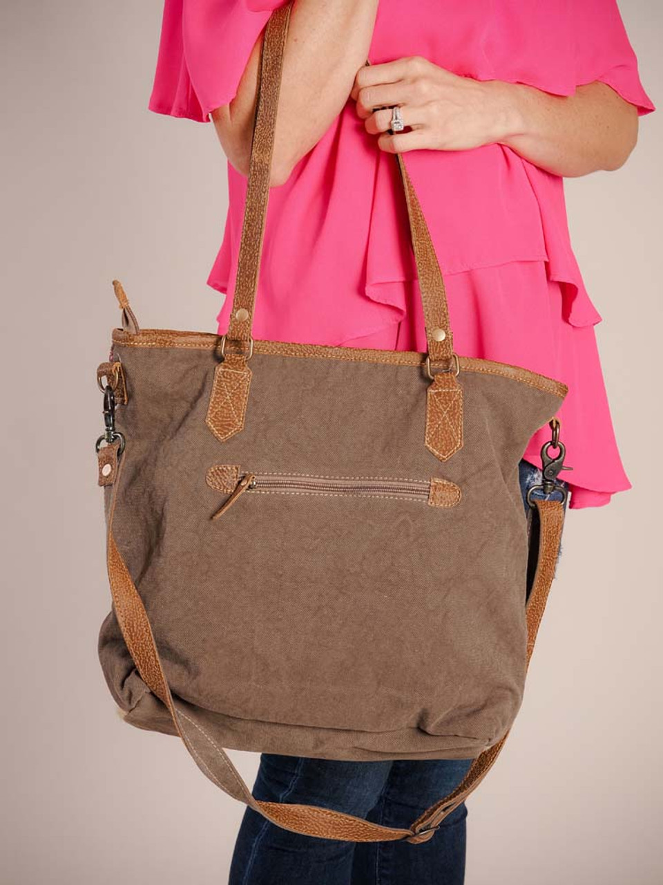 This brightly colored weekender bag has ample space to hold all your belongings for a short trip. Leather details; hairon accents at bottom of front; canvas back and bottom; zipper pocket on back; leather shoulder straps and adjustable/detachable crossbody strap; zipper close; fully lined inside with a zipper pocket and two slip pockets.
