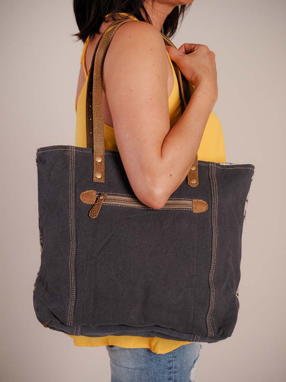Whimsical combination of handwoven pattern in the front with snake pattern on the side. Leather details; hairon accents on sides of front; canvas back and bottom; zipper pocket on back; leather shoulder straps; zipper close; fully lined inside with a zipper pocket and two slip pockets