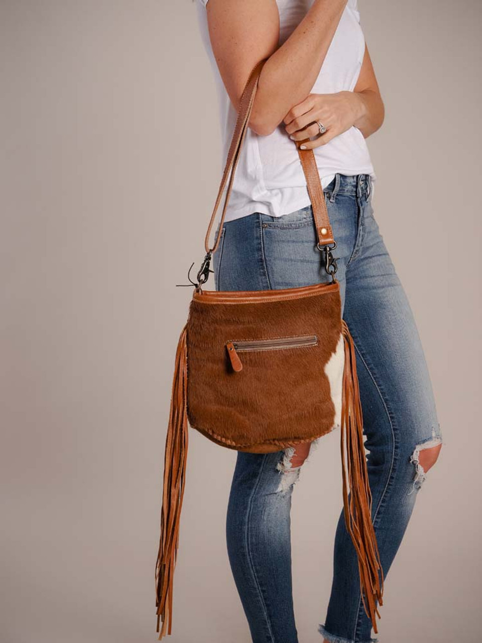 Retro cowhide bag with leather stitching and long fringe. Zipper pocket at back; zipper close at top; interior is fully lined and has one zipper pocket and two slip pockets