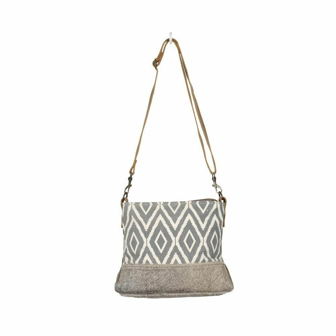 Great statement canvas bag that you can carry every day. Hairon accent at bottom of front; adjustable/removable strap gives options to carry on your shoulder or as a crossbody; zipper pocket at back; zipper close at top; interior is fully lined and has one zipper pocket and two slip pockets
