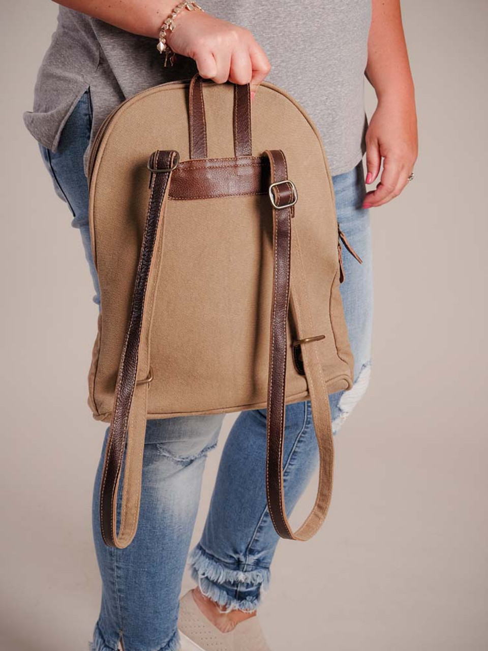 This backpack has an artistic design that was borrowed from an upcycled unique handwoven rug; hairon accent on front; leather details; zipper pocket on front; zipper close with two pulls zips wide open from half way up one side of the bag to half way down the other side; canvas back and bottom; handle and adjustable shoulder straps; fully lined interior with two slip pockets and a zipper pocket.