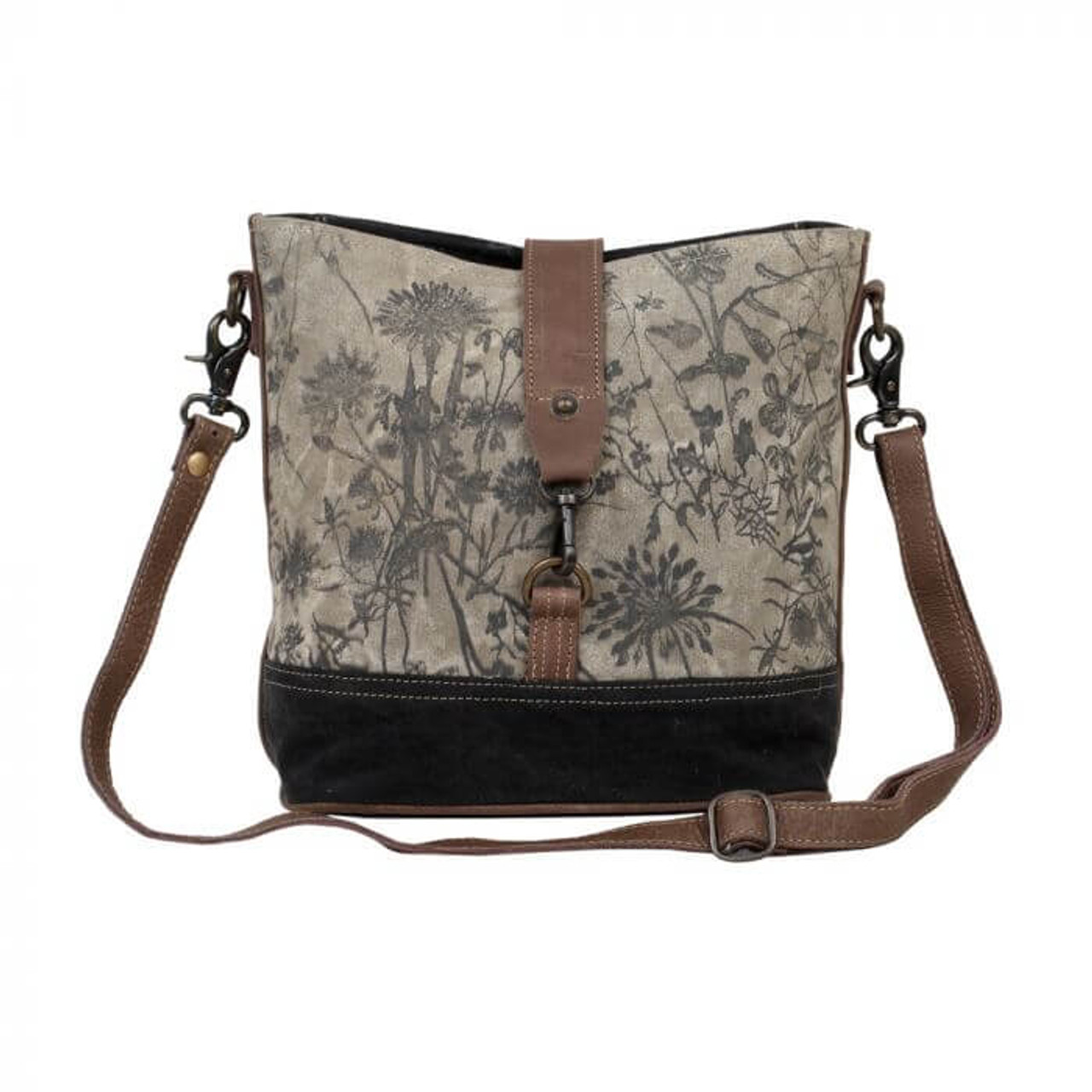 Botanical print on canvas with coordinating canvas bottom and back and leather details. Adjustable/removable shoulder strap gives options to carry on your shoulder or as a crossbody; zipper pocket at back; zipper close at top and leather flap that clips to bottom of bag; interior is fully lined and has one zipper pocket and two slip pockets.