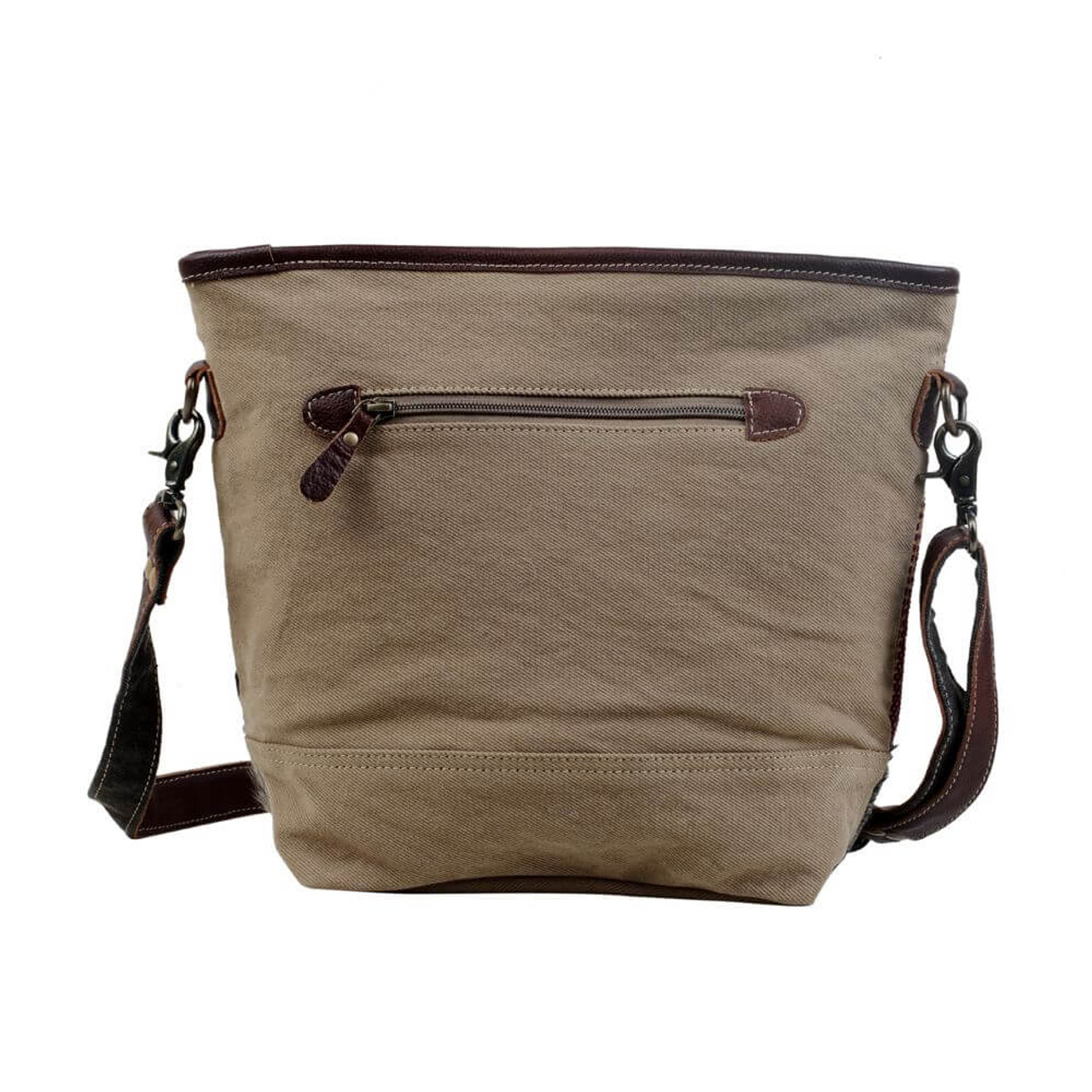This shoulder bag has bands of pattern interlaced to form a piece with an artistic vibe. The grey cowhide portion used at the bottom gives it a sturdy base. Canvas back and bottom, zipper pockets on front and back; adjustable/removable shoulder strap; zipper close at top; interior is fully lined and has one zipper pocket and two slip pockets