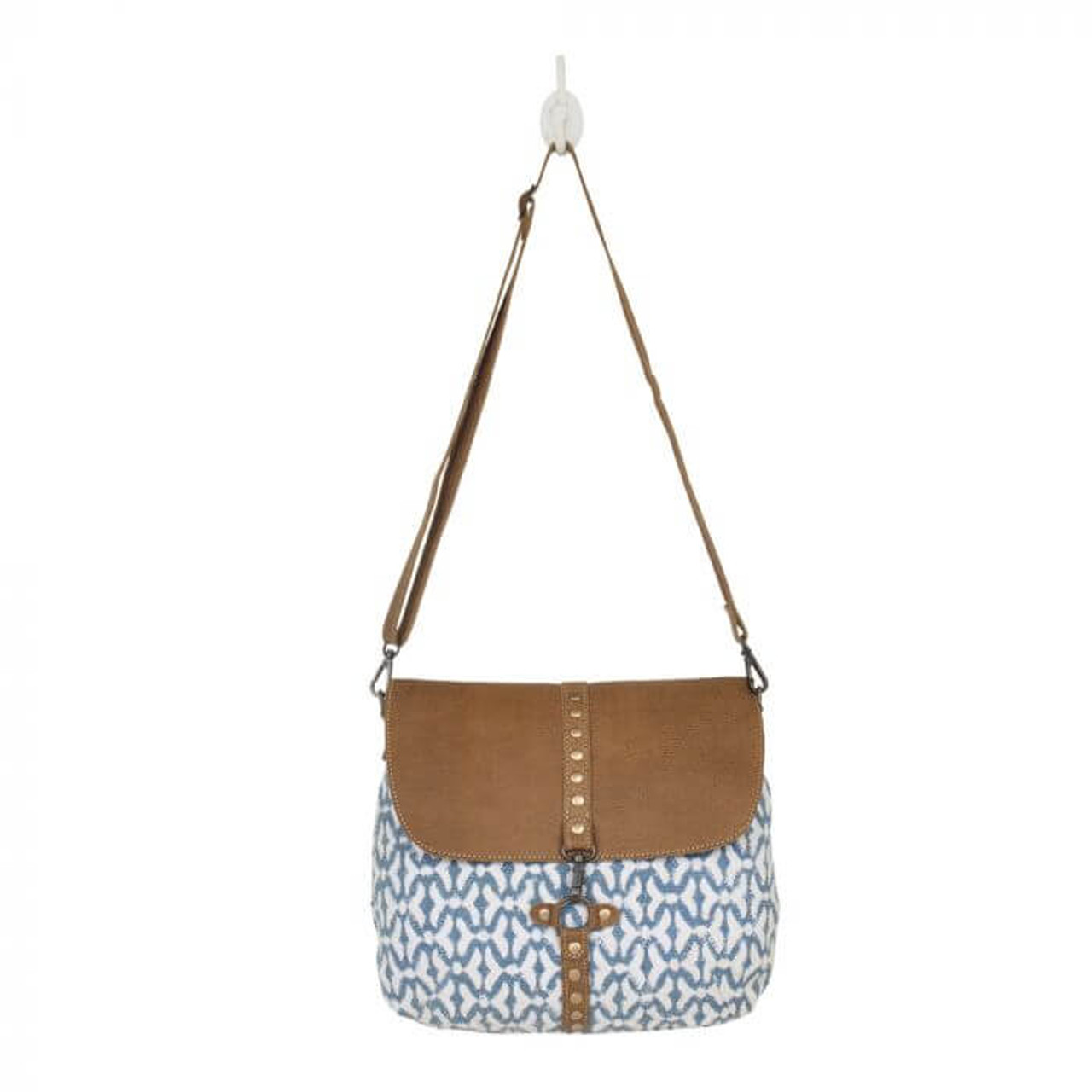 The perfect contrast of blue and white upcycled woven rug and leather with matte finished golden accents. Zipper pockets on back; adjustable/removable shoulder strap; zipper close at top and leather fold-over that clips to the front of the bag; interior is fully lined and has one zipper pocket and two slip pockets.