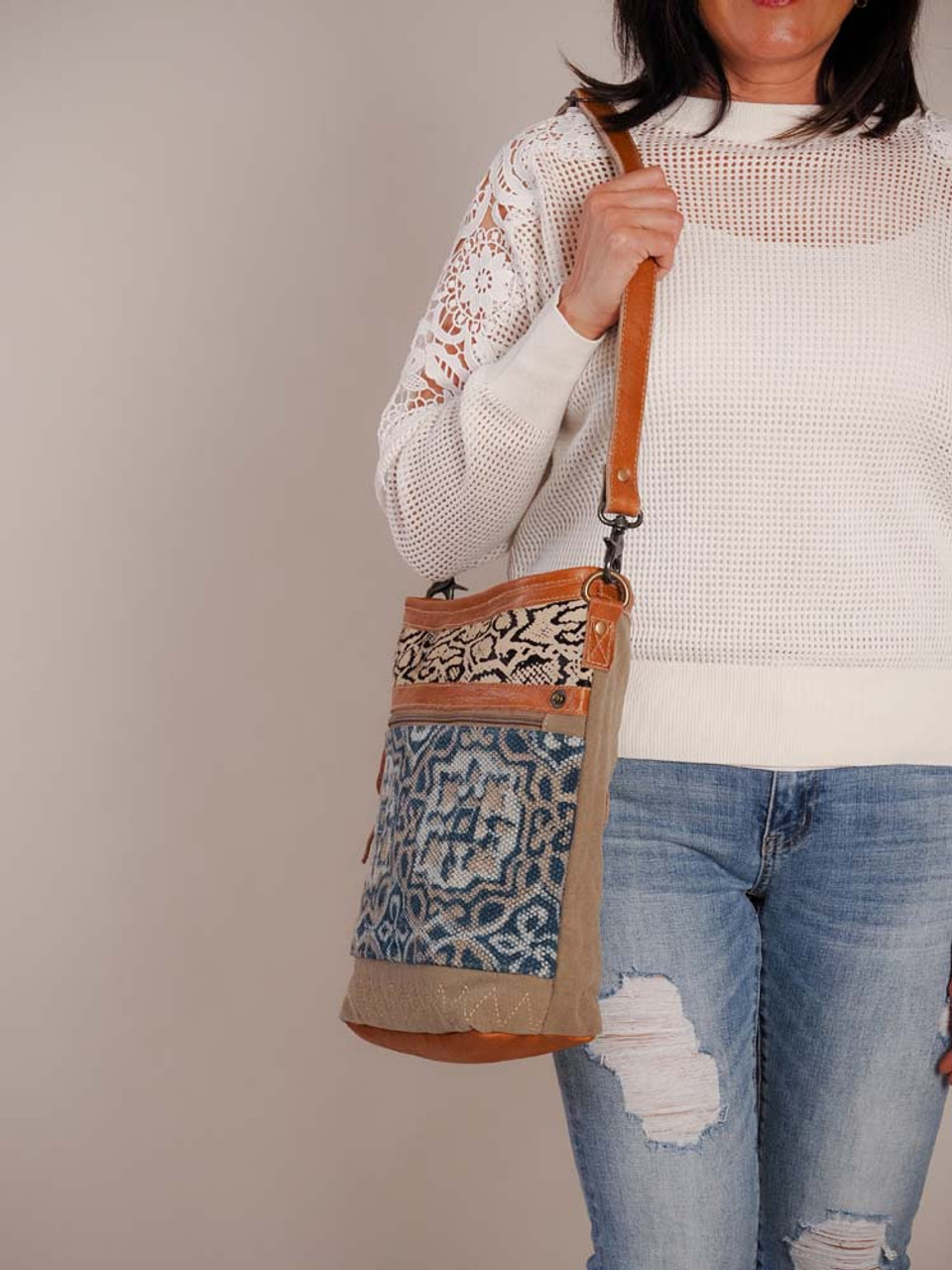 A unique blend of snake-print cowhide, azure pattern, and zig-zag stitching at the bottom. Leather details and bottom; canvas back; zipper pockets on front and back; adjustable/removable shoulder strap; zipper close at top; interior is fully lined and has one zipper pocket and two slip pockets.