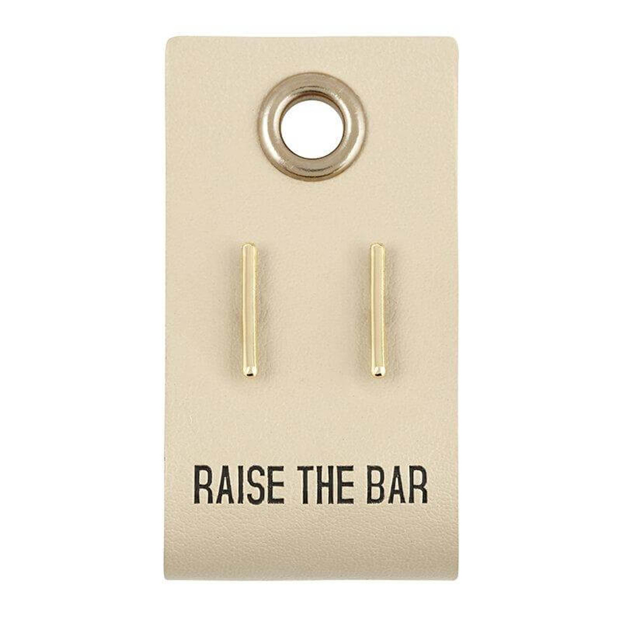 """""""Raise the bar"""" sentiment stamped on a 1"""" x 2"""" leather tag with .5"""" tiny bar stud earrings."""