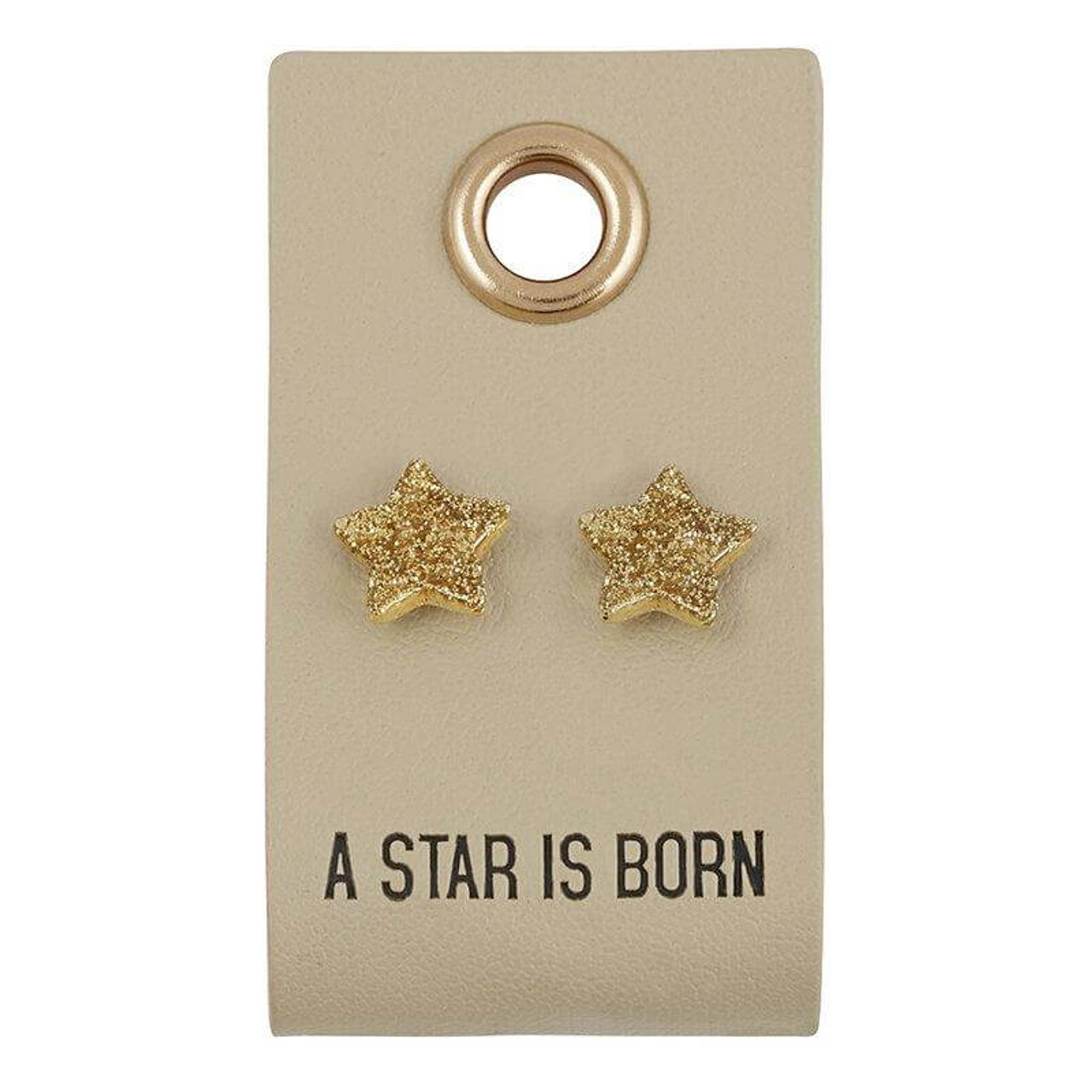 """""""A STAR IS BORN"""" sentiment stamped on a 1"""" x 2"""" leather tag with 3/8"""" tiny star stud earrings."""