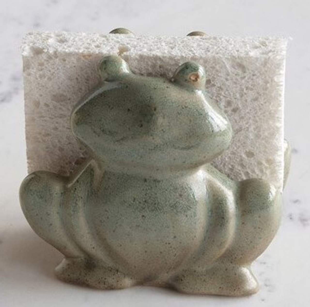 """This nostalgic stoneware frog sponge holder will cheer up any kitchen sink. 4-3/4"""" L x 3"""" W x 4"""" H; green reactive glaze (color will vary slightly from item shown)."""
