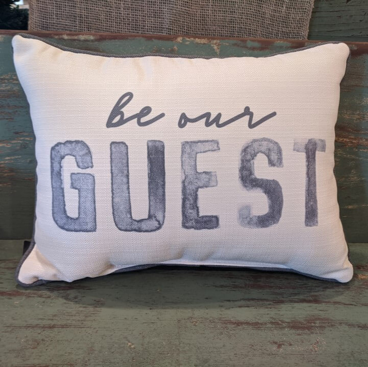"""The perfect way to cozy up any space! """"Be our guest"""" sentiment is dyed directly into the fabric, so it won't peel or crack; grey piping around the edge for an extra pop! Made from a soft yet durable polyester fabric, your pillow will arrive stuffed with poly-fill and sewn shut. Approx. 20"""" W x 14"""" H; machine washable in cold water, delicate cycle- fluff, air dry flat."""