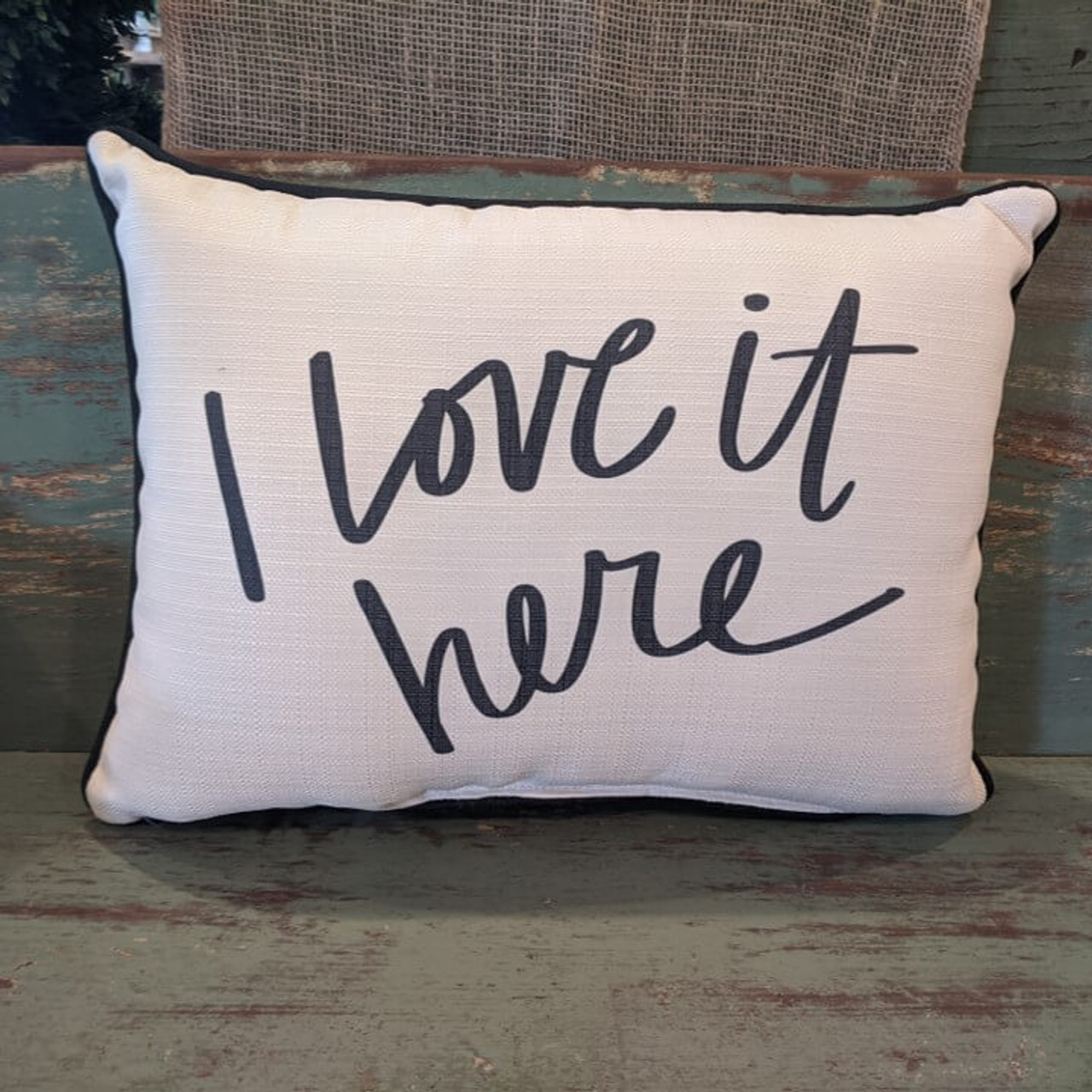 """The perfect way to cozy up any space! """"I Love it here"""" sentiment is dyed directly into the fabric, so it won't peel or crack; black piping around the edge for an extra pop! Made from a soft yet durable polyester fabric, your pillow will arrive stuffed with poly-fill and sewn shut. Approx. 20"""" W x 14"""" H; machine washable in cold water, delicate cycle- fluff, air dry flat."""