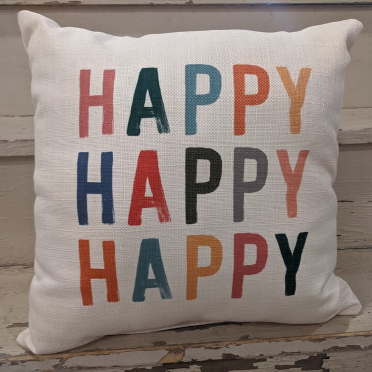 """The perfect way to cozy up any space! """"HAPPY HAPPY HAPPY"""" sentiment is dyed directly into the fabric, so it won't peel or crack. Made from a soft yet durable polyester fabric, your pillow will arrive stuffed with poly-fill and sewn shut. Approx. 17"""" square; machine washable in cold water, delicate cycle- fluff, air dry flat."""