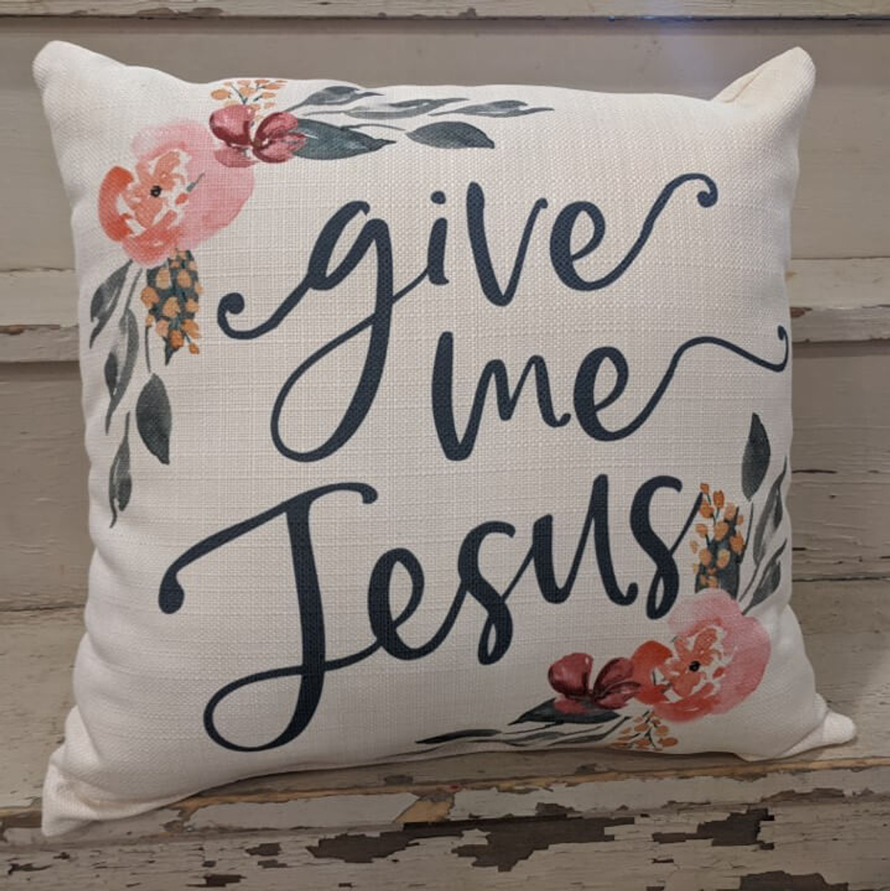 """The perfect way to cozy up any space! """"give me Jesus"""" sentiment and floral design are dyed directly into the fabric, so it won't peel or crack. Made from a soft yet durable polyester fabric, your pillow will arrive stuffed with poly-fill and sewn shut. Approx. 17"""" square; machine washable in cold water, delicate cycle- fluff, air dry flat."""