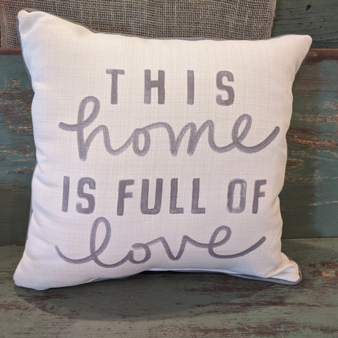 """The perfect way to cozy up any space! """"THIS home IS FULL OF love"""" sentiment is dyed directly into the fabric, so it won't peel or crack; grey piping around the edge for an extra pop! Made from a soft yet durable polyester fabric, your pillow will arrive stuffed with poly-fill and sewn shut. Approx. 17"""" square; machine washable in cold water, delicate cycle- fluff, air dry flat."""