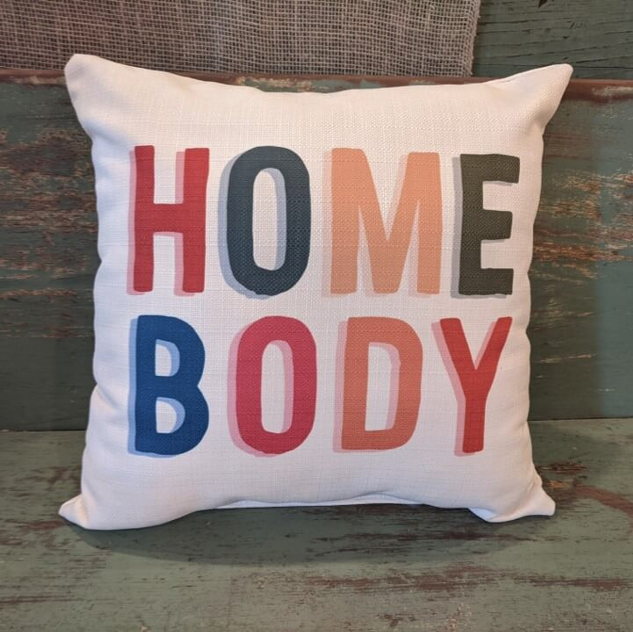 """The perfect way to cozy up any space! """"HOME BODY"""" sentiment is dyed directly into the fabric, so it won't peel or crack. Made from a soft yet durable polyester fabric, your pillow will arrive stuffed with poly-fill and sewn shut. Approx. 17"""" square; machine washable in cold water, delicate cycle- fluff, air dry flat."""