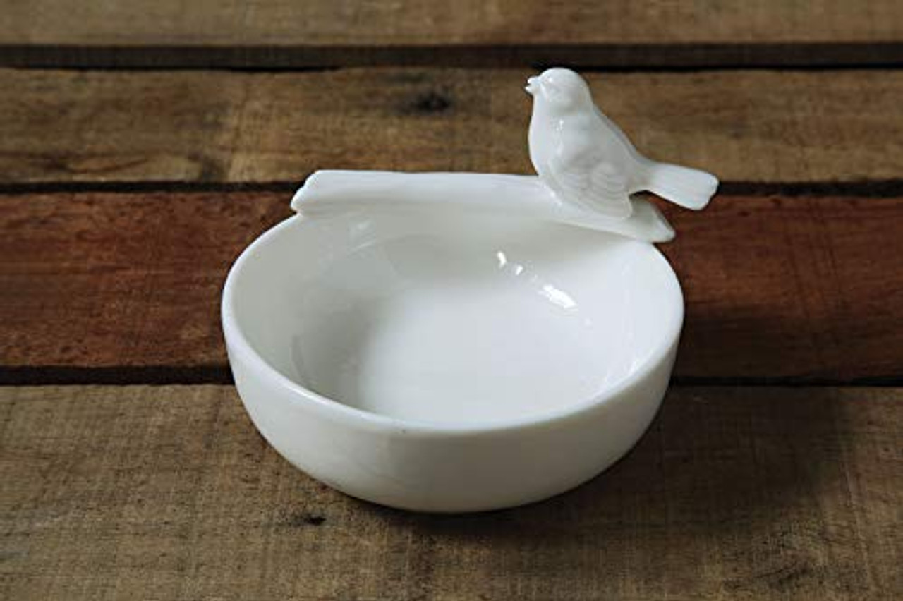"""Stone/white ceramic bowl with bird perching on a branch. Bowl is 4.25"""" round, 1.5"""" high (3"""" high including the bird)."""