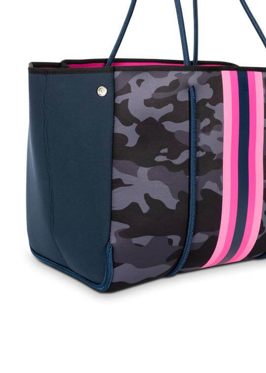 """Navy camo neoprene crossbody with pinks & navy stripe.  This neoprene tote is the perfect blend of style and functionality.   Ultra light weight.  Side panels expand for a phantom shape or snap in for a streamline look.  Fashionable and sturdy rope detail and shoulder straps.  Removable hard bottom liner.  Removable wristlet pouch.  Washable with mild soap. Hang dry. Hand wash recommended.  Dimensions- 18"""" W with side panels expanded (14.4"""" W with side panels snapped closed) x 12"""" T x 10"""" D.  Pouch measures 8.5 inches wide by 6 inches tall."""