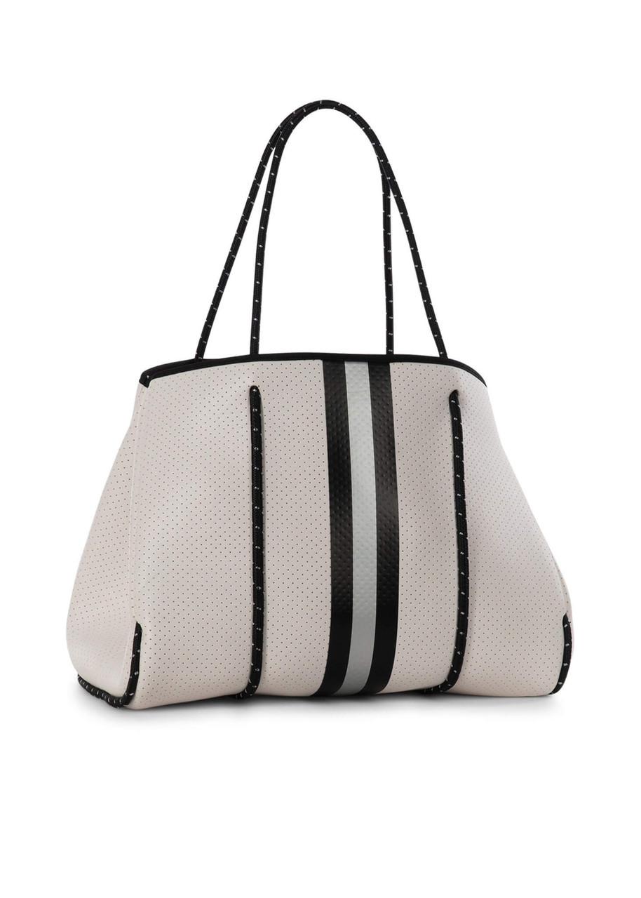 """Solid whitecoated perforated neoprene with black/white straps, black/grey stripe, and red lining  This neoprene tote is the perfect blend of style and functionality.   Ultra light weight  Side panels expand for a phantom shape or snap in for a streamline look  Removable hard bottom liner  Removable wristlet pouch  Washable with mild soap. Hang dry. Hand wash recommended.  Dimensions:18"""" W with side panels expanded (14.4"""" W with side panels snapped closed) x 12"""" T x 10"""" D.a  Pouch measures 8.5 inches wide by 6 inches tall"""