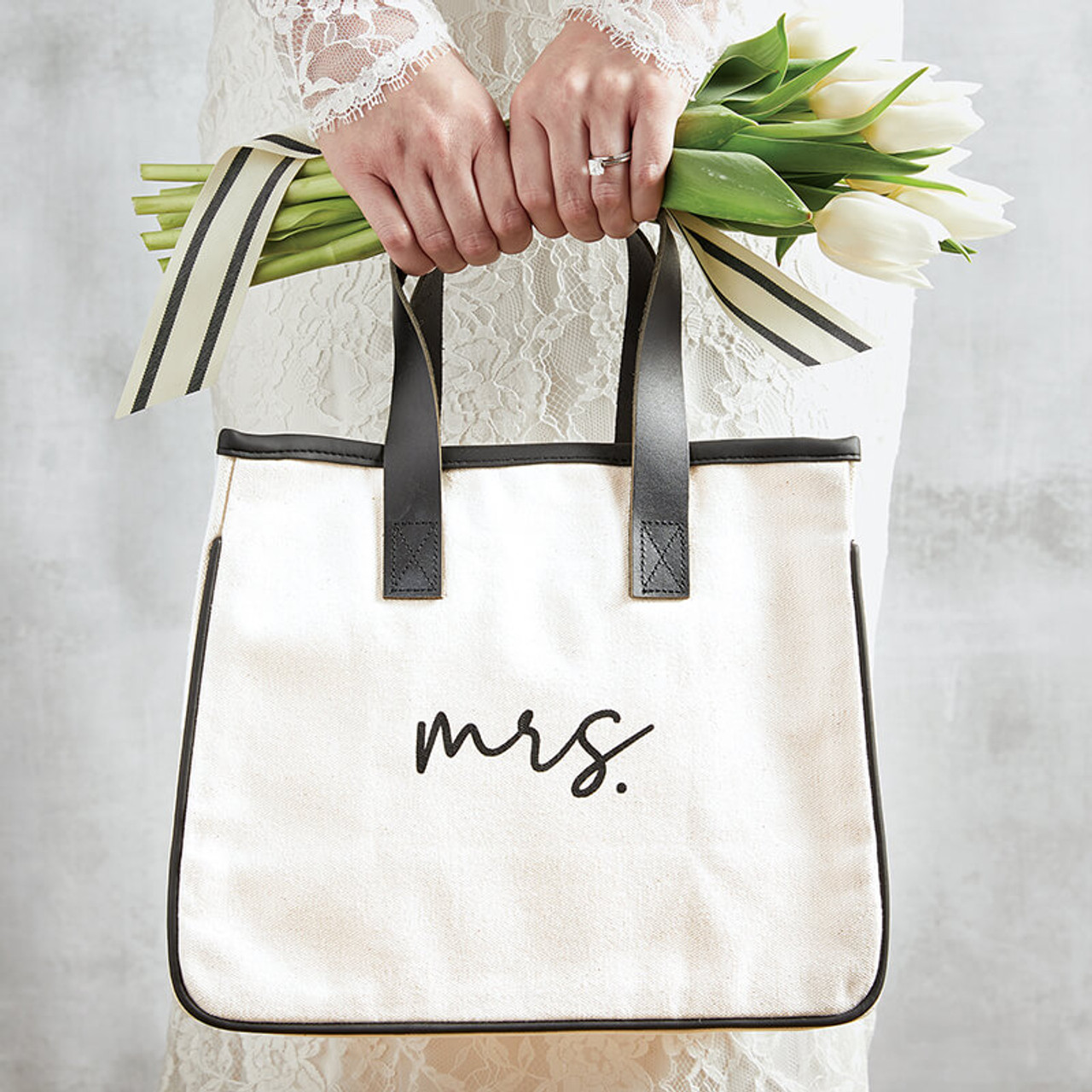 """Small and easy to tote around your wedding day and then everyday essentials! Canvas and genuine leather; 10"""" L x 12"""" W x 6.5"""" D, 5.25"""" handle drop."""