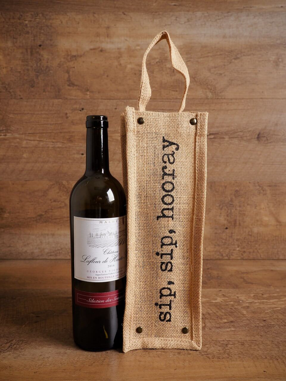 "A Bottle of Wine Next to A Canvas Bag With the Printed Saying ""Sip, Sip, Hooray."""
